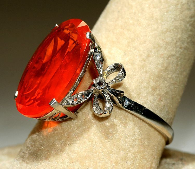 Art Deco ring: huge fire opal flanked by diamond bows. Yes, please.