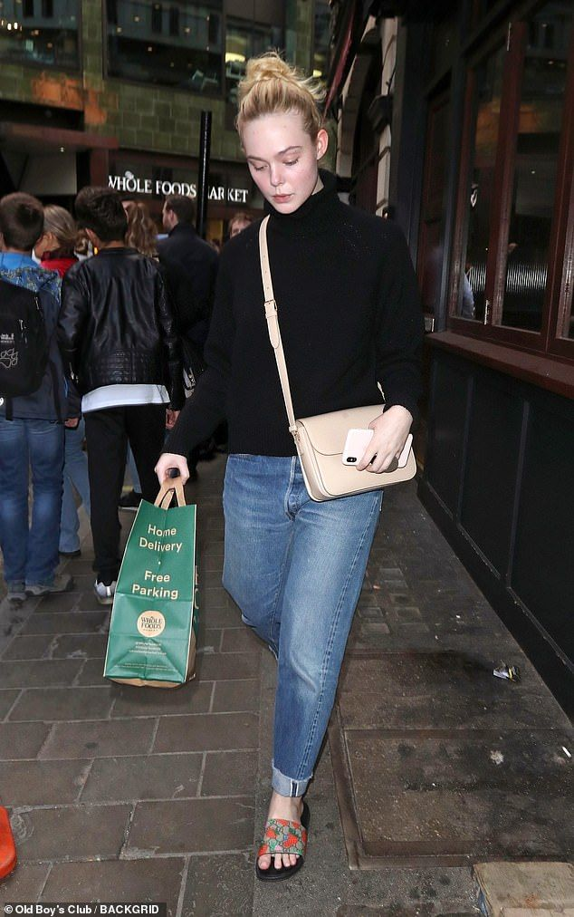 Dressed down: Elle looked cool and casual in an oversized black knit teamed with loose boy... #ellefanning #streetstyle