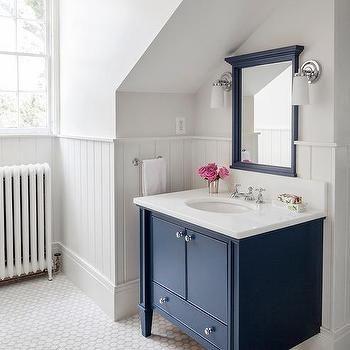 cottage bathroom features a beautiful dark navy washstand