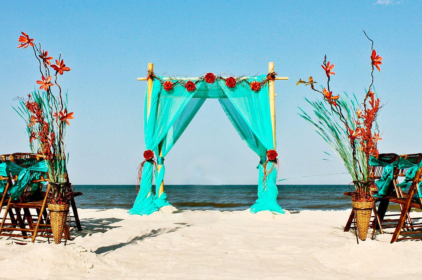 Turquoise/aqua and red/orange are one of my favorite color combinations for a beach wedding. I love how those colors are incorporated I to the chair and aisle decor as well.