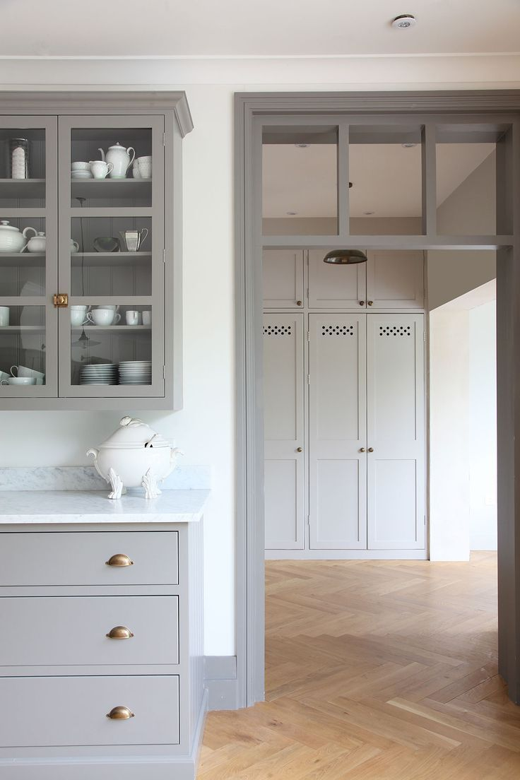 White And Light Grey Kitchen gray kitchen cabinets, brass hardware, herringbone floor
