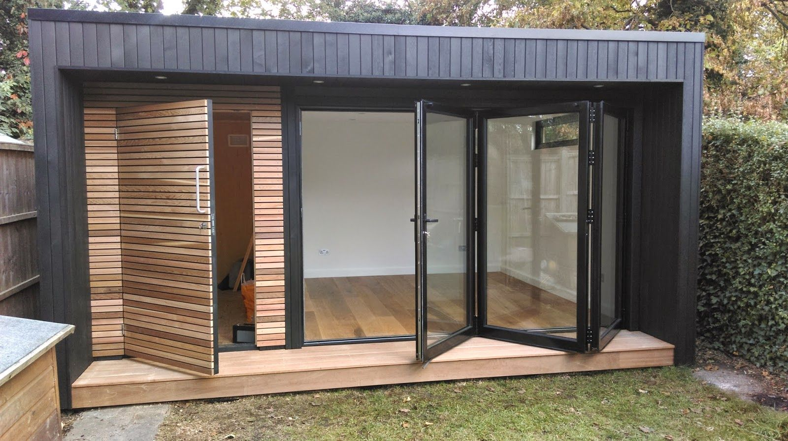 Garden room with contrasting cedar cladding and bi fold for Cedar garden office
