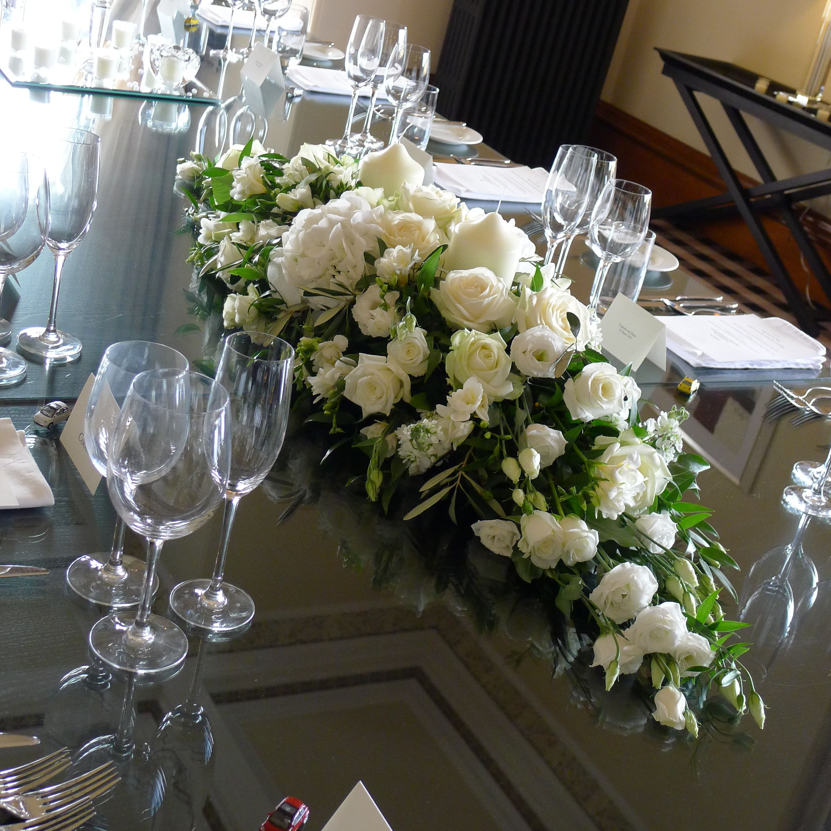 A long and low table centrepiece made up of whites creams for Rose centerpieces for wedding tables