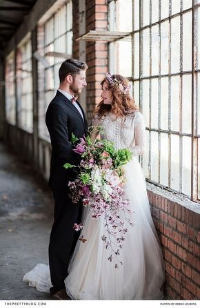 A romantic wedding with a long sleeved lace dress and a soft skirt in anabandoned warehouse