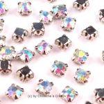 Strasssteine zum Annähen 4,5 mm transparent irisierend - diese funkelnden Strasssteine haben eine Metallfassung mit vier Löchern zum sicheren Annähen an Taschen, Kleidern oder auch zum Herstellen von Modeschmuck und mehr.Die Strasssteine sind aus Glas und funkeln herrlich. Größe: 4,5 mmInhalt: 20 Stück