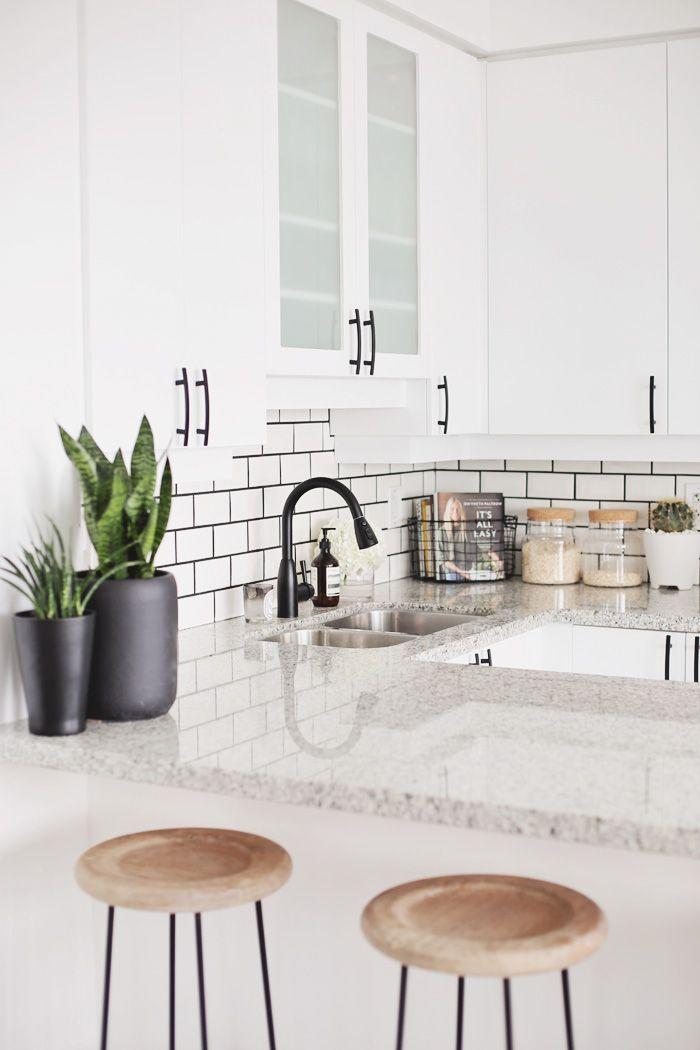 granito gris, muebles y paredes blancas. guarda dorada.   Cocinas ...