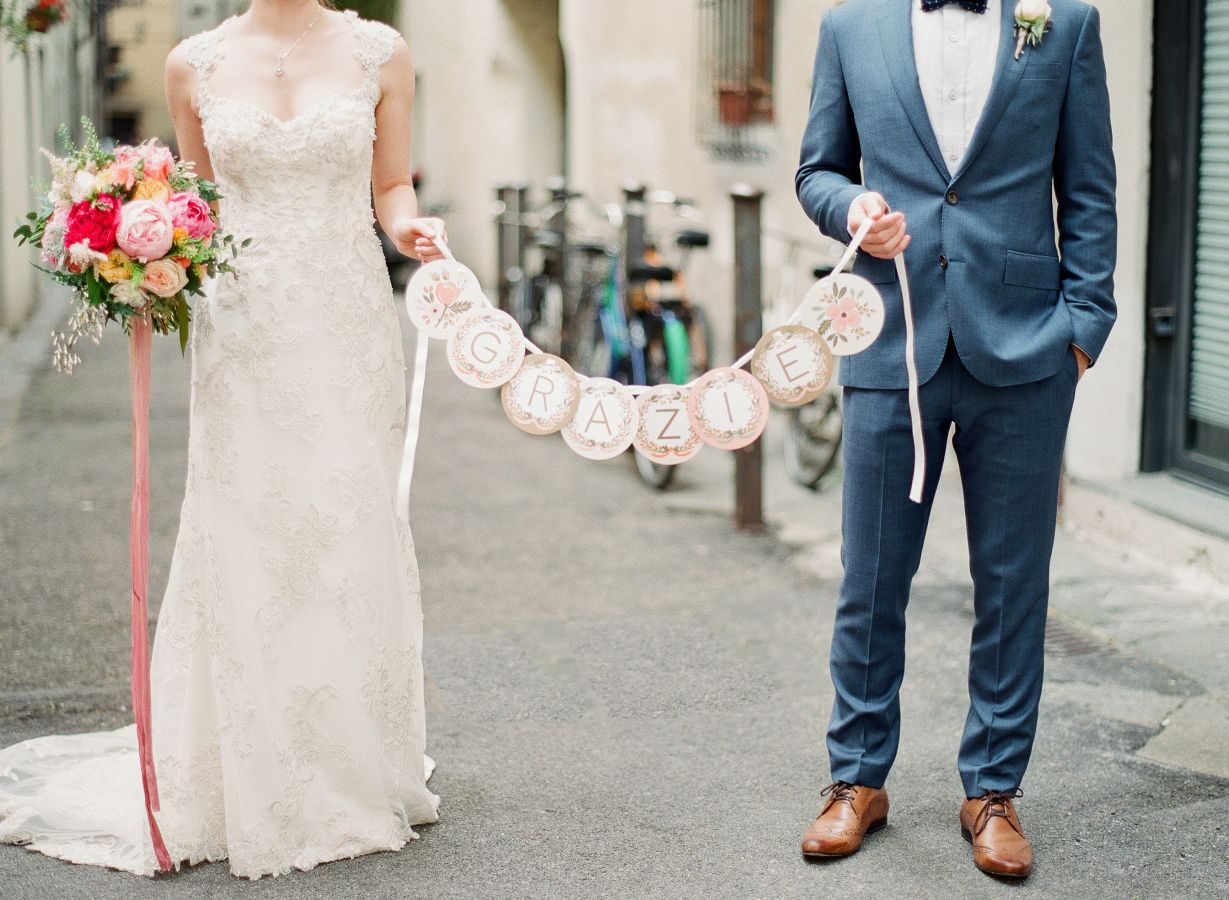 bride-and-groom-holding-thanks-sign http://itgirlweddings.com/everything-need-know-plan-wedding-abroad/