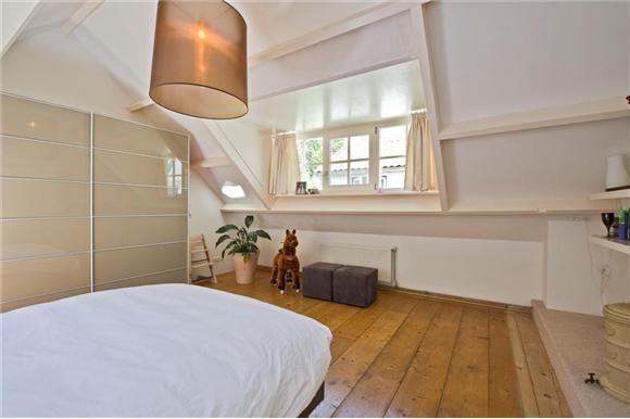 Slaapkamer met houten vloer punt dak nok en dakkapel met