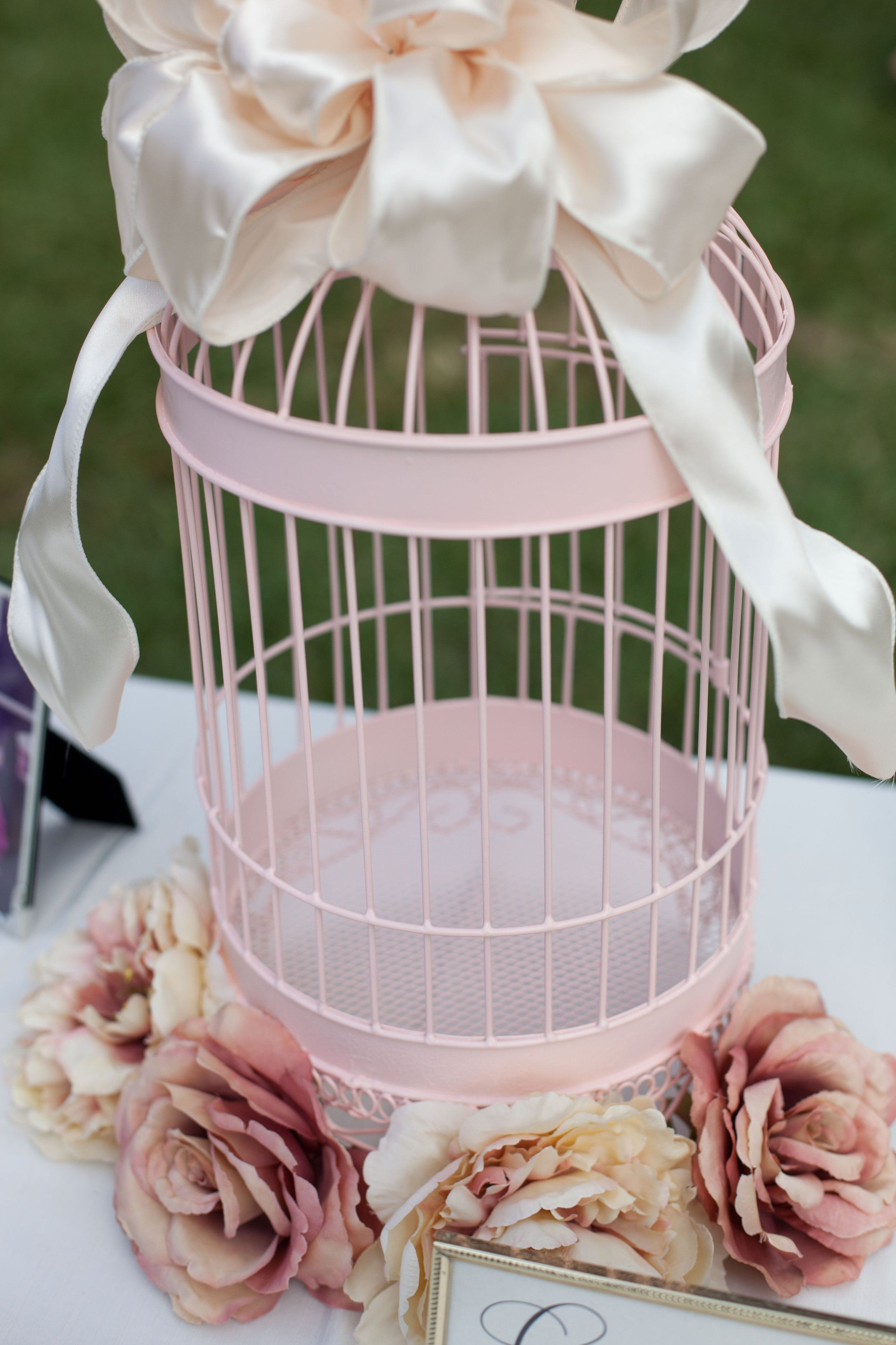 White bird cage spray painted pink Ivory satin bow on top and