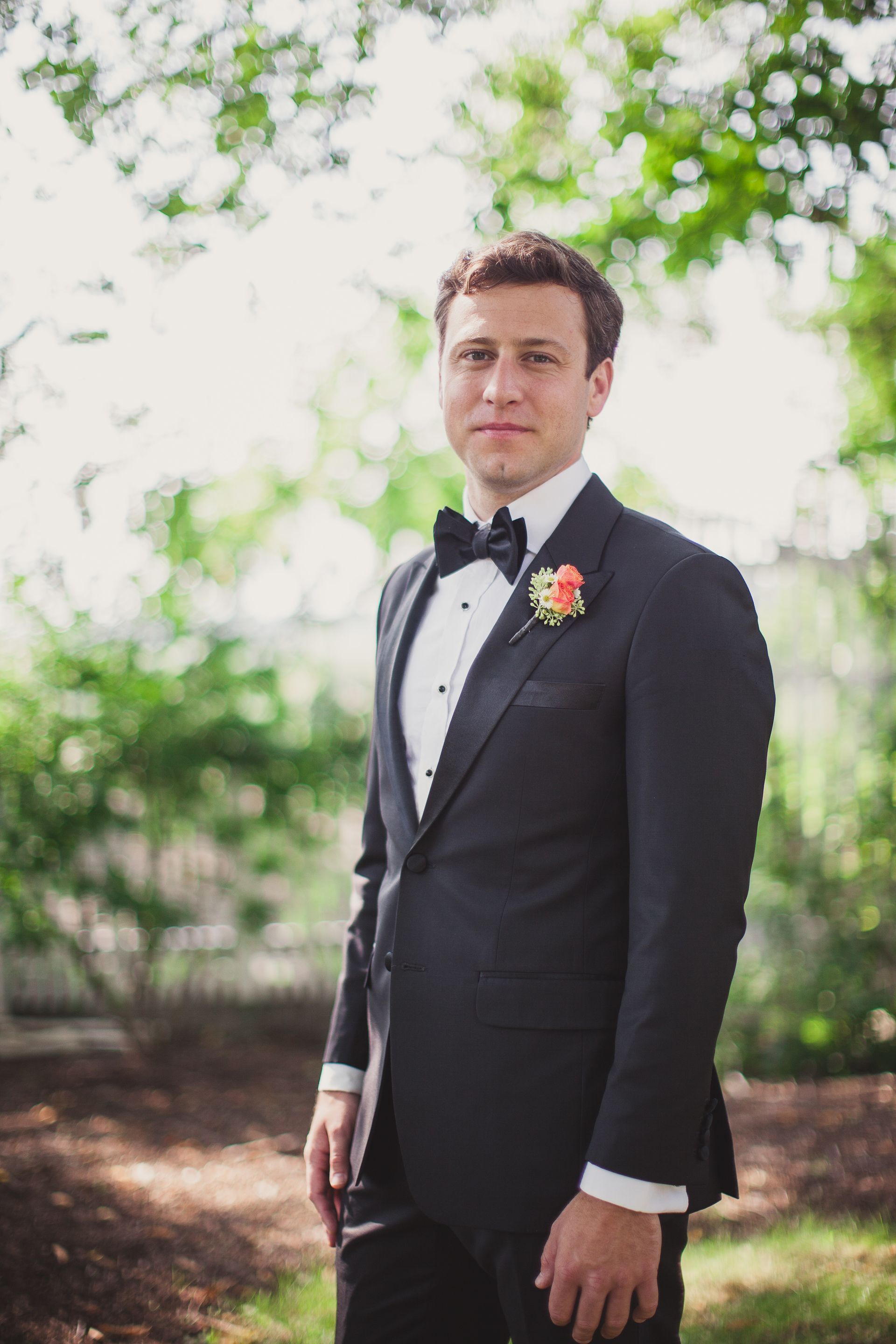 Classic formal groom attire, black bowtie, bright coral boutonniere // Mariana Feely Photography