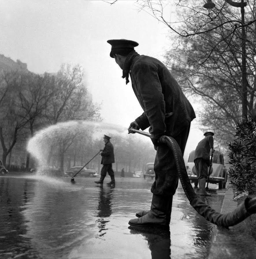 Operario regando el Paseo de Recoletos de Madrid (1953). Fotografía de Francesc Català-Roca.