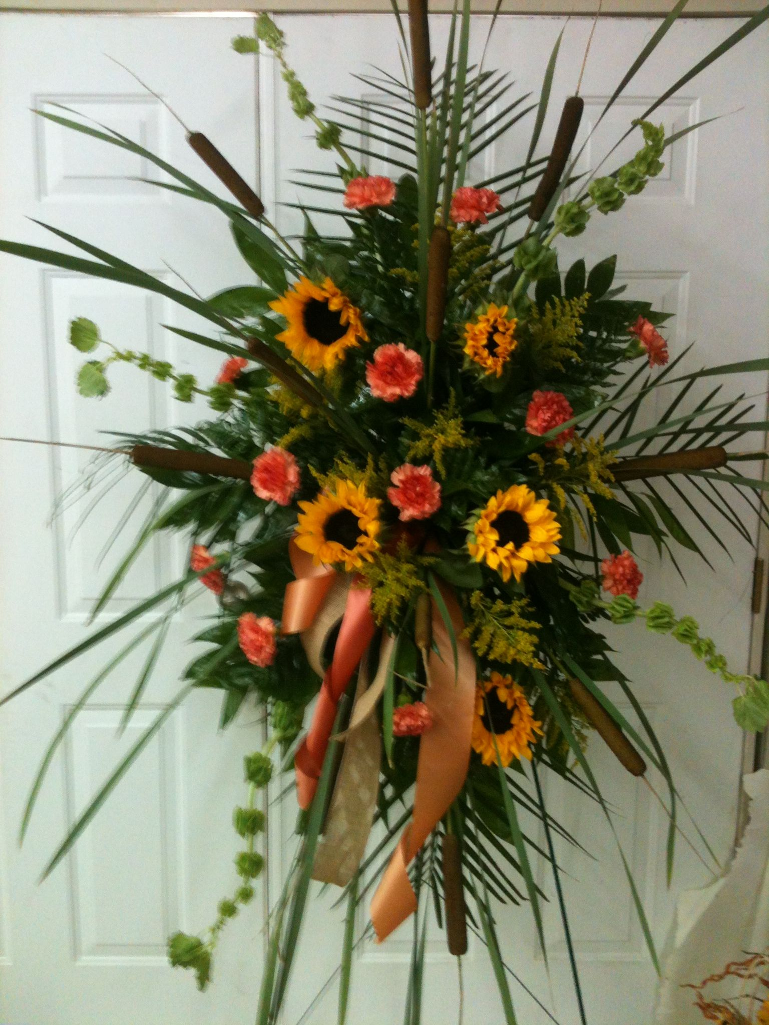 Funeral spray with cattails sunflowers orange carnations