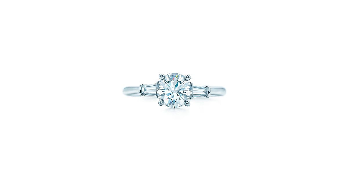 Tapered baguette side stones draw the eye toward the remarkable round brilliant center stone.