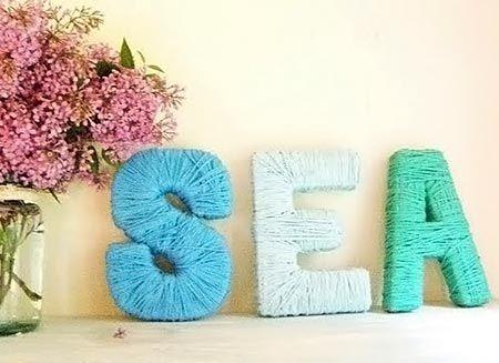 Letras cobertas com fios de lã coloridos