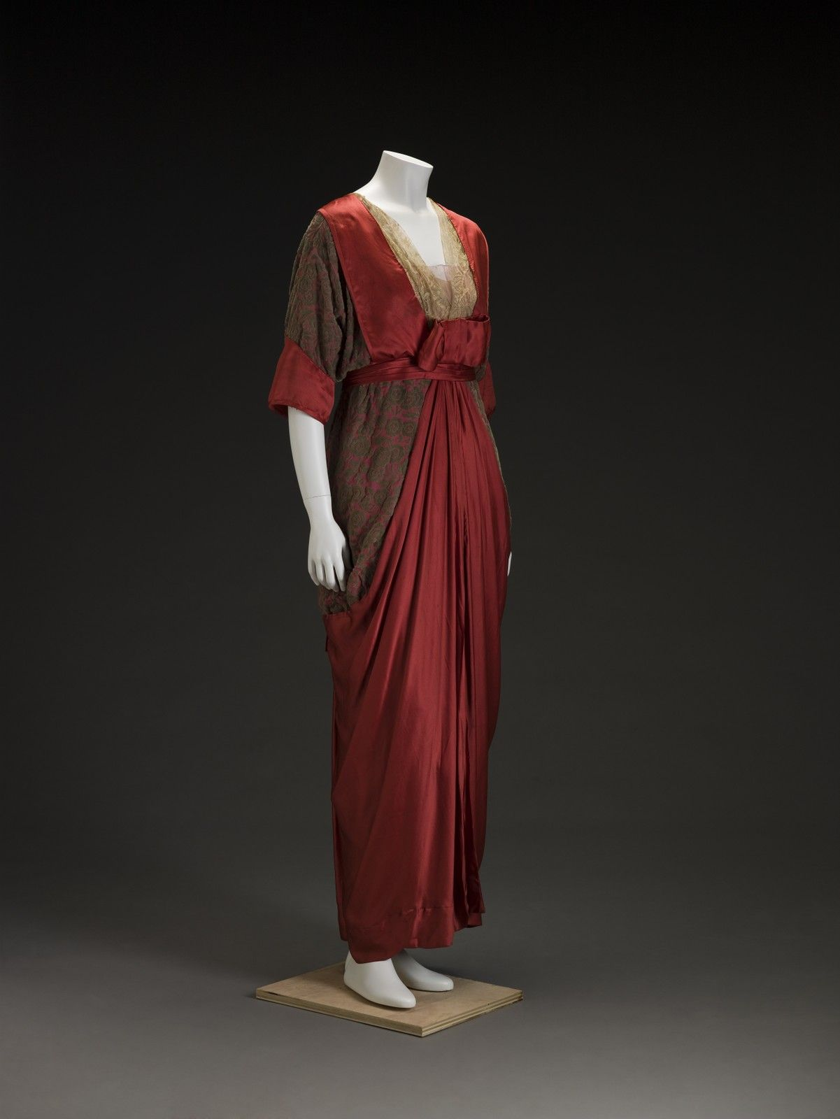 Dress, American, ca. 1910s. The voided silk velvet fabric, with its pattern of stylized roses, complements the graceful draping of the vibrantly colored silk satin fabric of this dress.