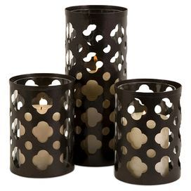 "Set of three iron candleholders with quatrefoil cut-outs.Product: 2 Small and 1 large candleholder  Construction Material: Wrought iron and glass  Color: Natural    Features:  Intricate peak-a-boo pattern crafted into the sidesTraditional style  Accommodates:  (1) Candle each - not included    Dimensions: Small: 6.25"" H x 4.5"" Diameter eachLarge: 10.75"" H x 4.5"" Diameter"