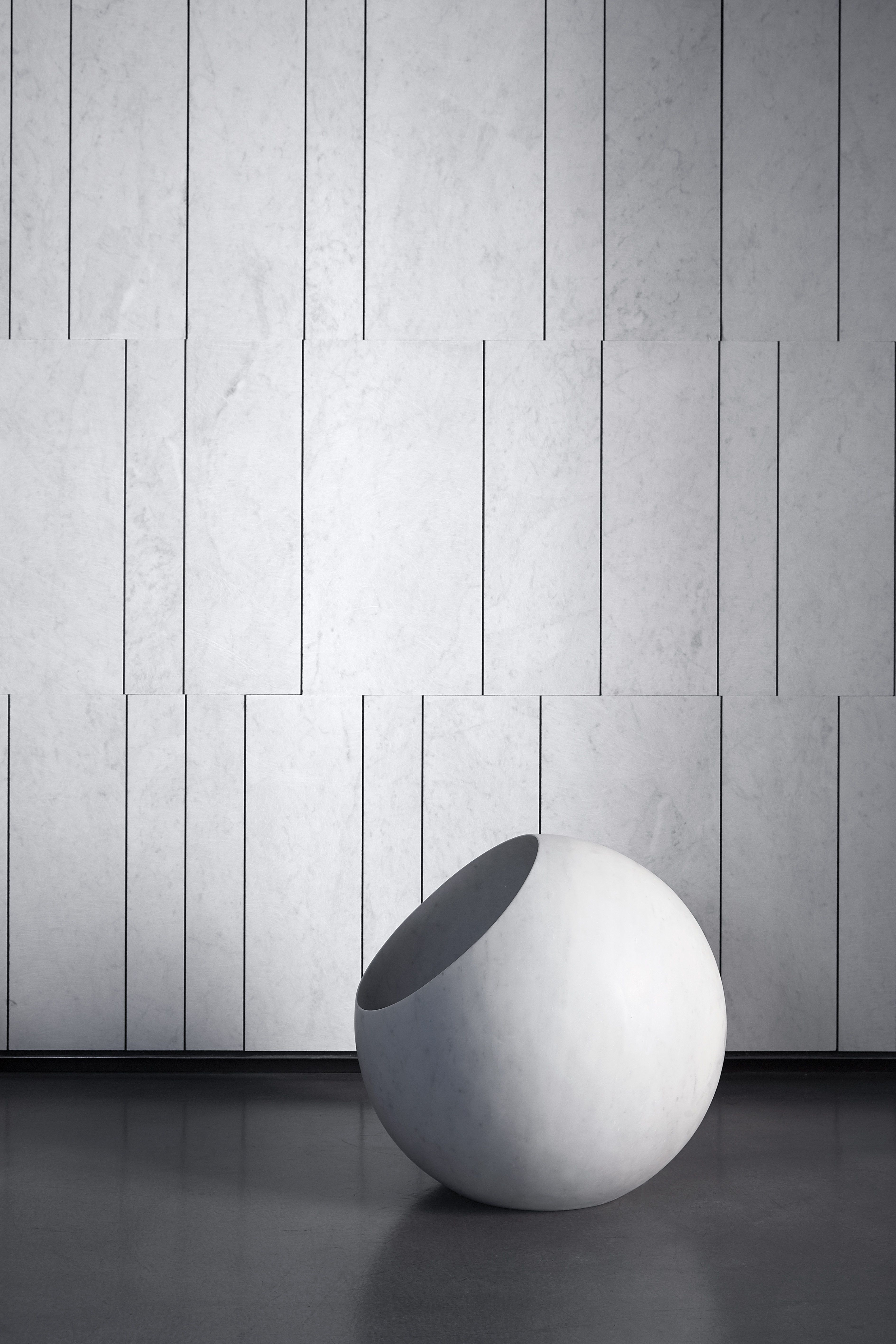 Urano collection. Urano, designed by Elisa Ossino, is a gorgeous sphere carved out of a cube of Bianco Carrara, shedding a soft and romantic light. Available in diameters of 18 and 30 cm for the table or 50 cm as a floor lamp.