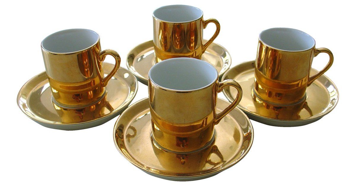 "Set of four Neiman Marcus demitasse cups and saucers, with bright gold color on the outside and white on inside. Original labels attached to undersides: ""Neiman Marcus Japan."" Four cups, 1.85""Dia x..."