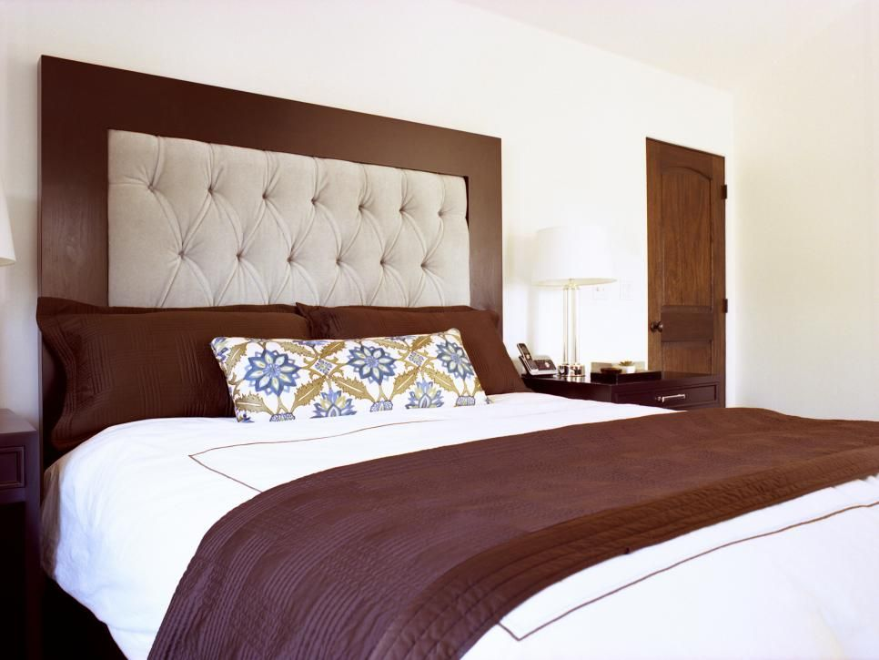 In this bedroom, a plush tufted headboard is framed with rich wood to create a dynamic juxtaposition above the bed. The bold brown and white color combo is carried throughout the room, from the linens and pillows to the nightstand and lamp.