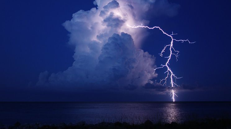 Photograph by Kara Swanson. Lightning arcs from the top of a cloud to the horizon off the coast of the Bahamas.