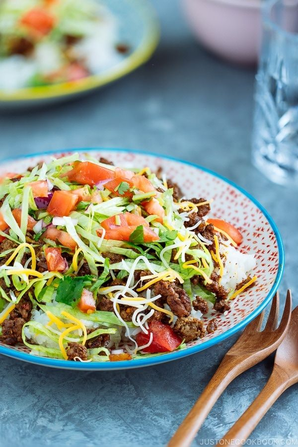 Okinawan Taco Rice is a fusion dish of Tex-Mex and Japanese food! It's an Okinawan specialty and popular among the US Military. Steamed rice topped with seasoned ground beef, tomatoes, and romaine lettuce. It's satisfyingly, unique comfort food that's quick to make for a weeknight dinner! #summerricebowlrecipes. #OkinawanFood #JapaneseFood #AsianFood #Okinawa #Tacoricerecipe #RiceBowls | Easy Japanese Recipes at JustOneCookbook.com