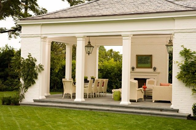 Loggia with southern white columns, lanterns and fireplace. Design by Elizabeth Dinkel