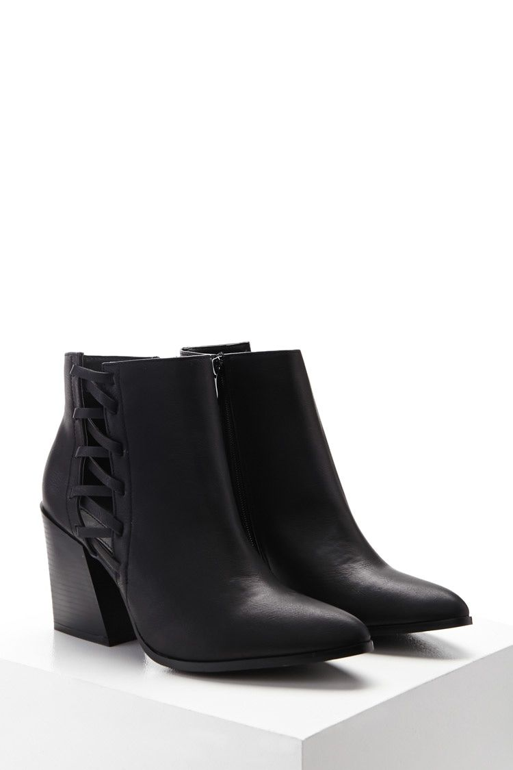 bee5cdcea88 A pair of faux leather ankle boots featuring a crisscross cutout panel