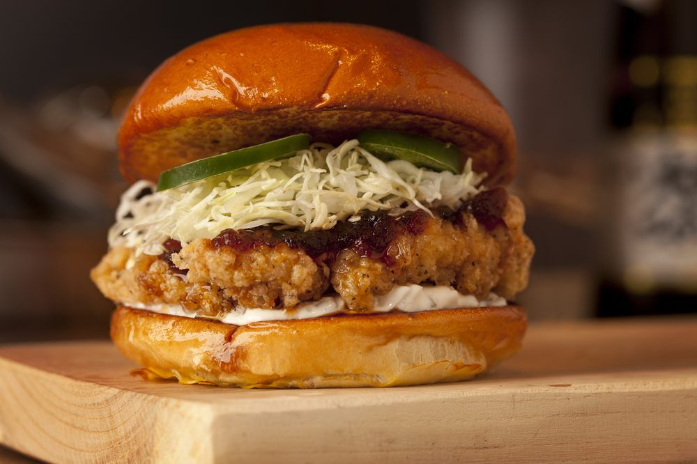 """The """"Nom Bomb"""" sandwich. A generous pice of sweet-and-sour, teriyaki-glazed, deep-fried chicken -- served on a toasted brioche bun with a handful of shredded cabbage, smear of creamy tartar sauce and slices of fiery jalapeno."""