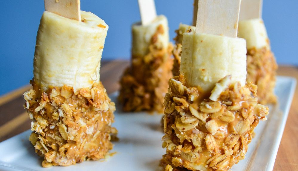 Snack Idea: Banana, Nut Butter & Granola -  Ingredients for 1 serving: 1/2 med banana, 1 tbsp natural peanut butter (or other nut butter), 1/8 cup raw granola (I used Bare Naked) -Steps: Warm choice of natural nut butter in microwave 10-15 secs. Slice a banana in half. Pour granola on a small plate. Dip  banana in the warm nut butter & roll the peanut butter portion of the banana in the granola. Put in the freezer or fridge