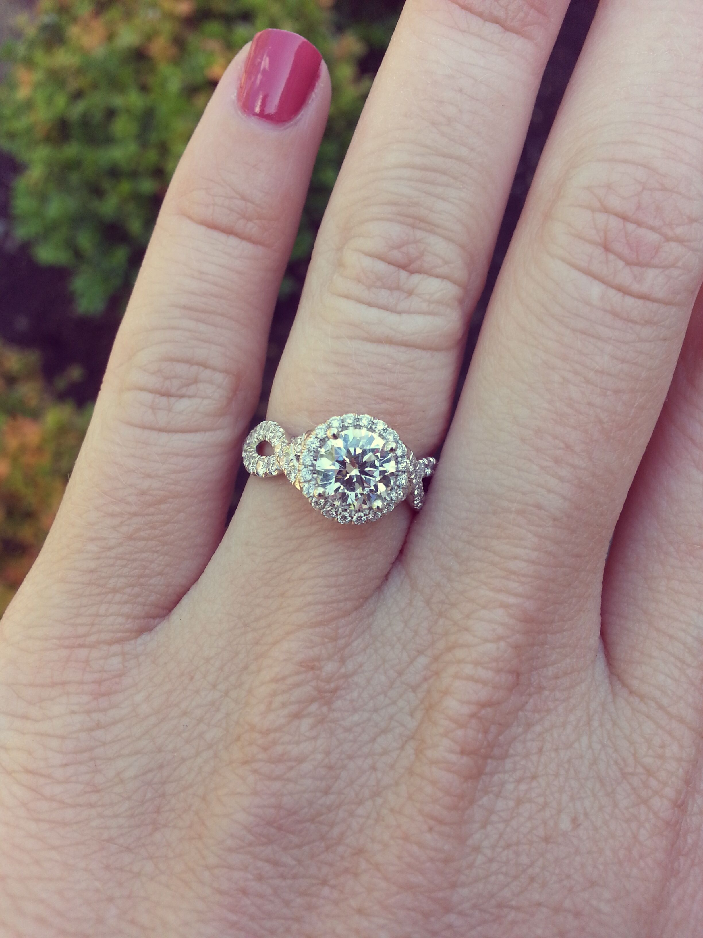 Custom round brilliant halo engagement ring with infinity twist side