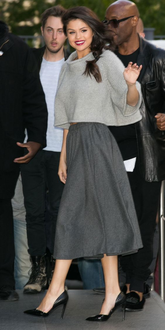 Selena Gomez in a cropped sweater and a gray midi skirt with black pumps.    13f335fade