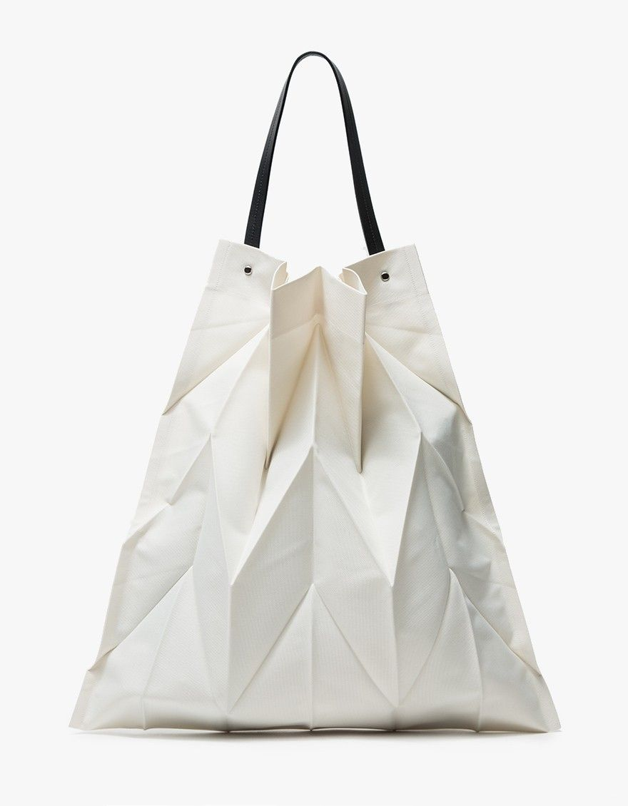 0789c4f3e66 Modern, textured tote from Iittala in collaboration Issey Miyake in Ivory.  Innovative pleating techniques add texture dimension. Black cowhide top  handle ...