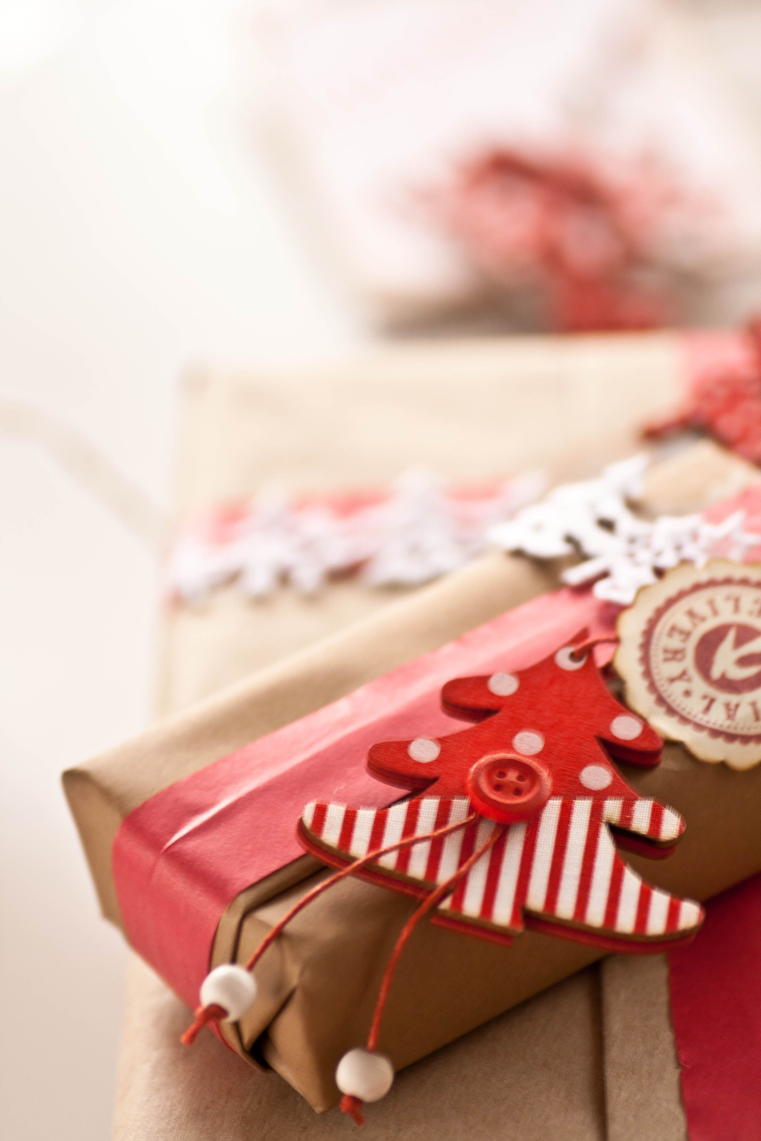 figurine de bois ou de feutrine épaisse, bouton, ficelle, décorant un simple paquet de kraft
