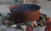Tractor Tire Rim Fire Pit. Can find one at a junk yard. Washing machine drums are another great idea to make a grill out of.