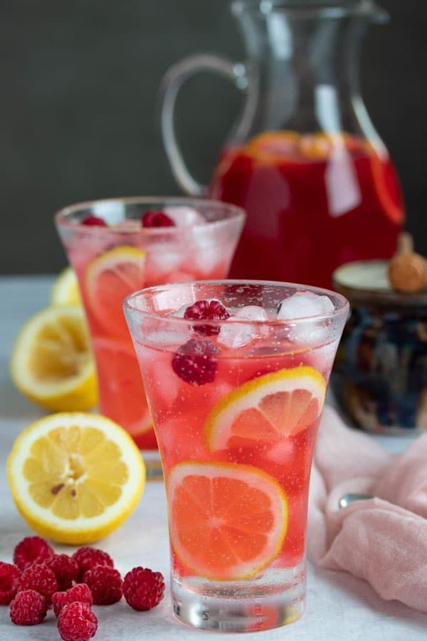 Hard Raspberry Lemonade and Limoncello Cocktail #limoncellococktails This hard raspberry lemonade and limoncello cocktail is going to become your new favorite summer cocktail!  It's refreshing, fruity and so so good! In this post we give you a recipe for making this as a single raspberry limoncello cocktail or as a pitcher of hard raspberry lemonade. This is a fabulous summer cocktail for summer parties! #cookswithcocktails #raspberrylemonade #limoncellococktails #raspberrycocktail #summercockt #limoncellococktails