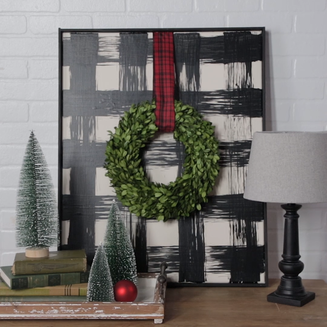 Combine buffalo check pattern with traditional Christmas decor for a creative DIY holiday decor. This large buffalo check artwork will add a cozy touch to your holiday mantel. We'll show you how to build your own with an inexpensive canvas. #buffalocheck #diyholidaydecor #manteldecor #holidaymantelideas #bhg