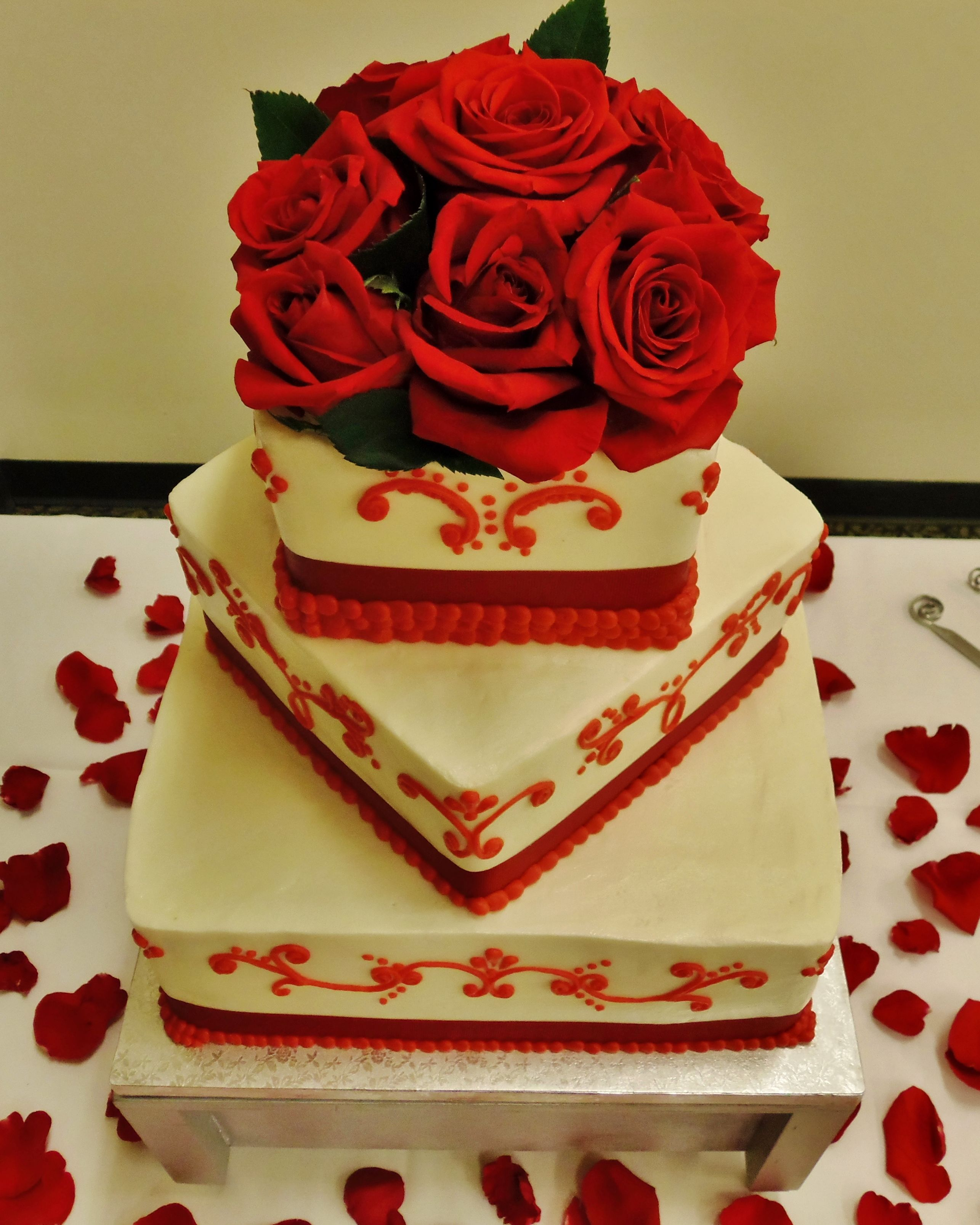 Red scrollwork wedding cake w/ fresh red roses & ribbon. 3-tier ...