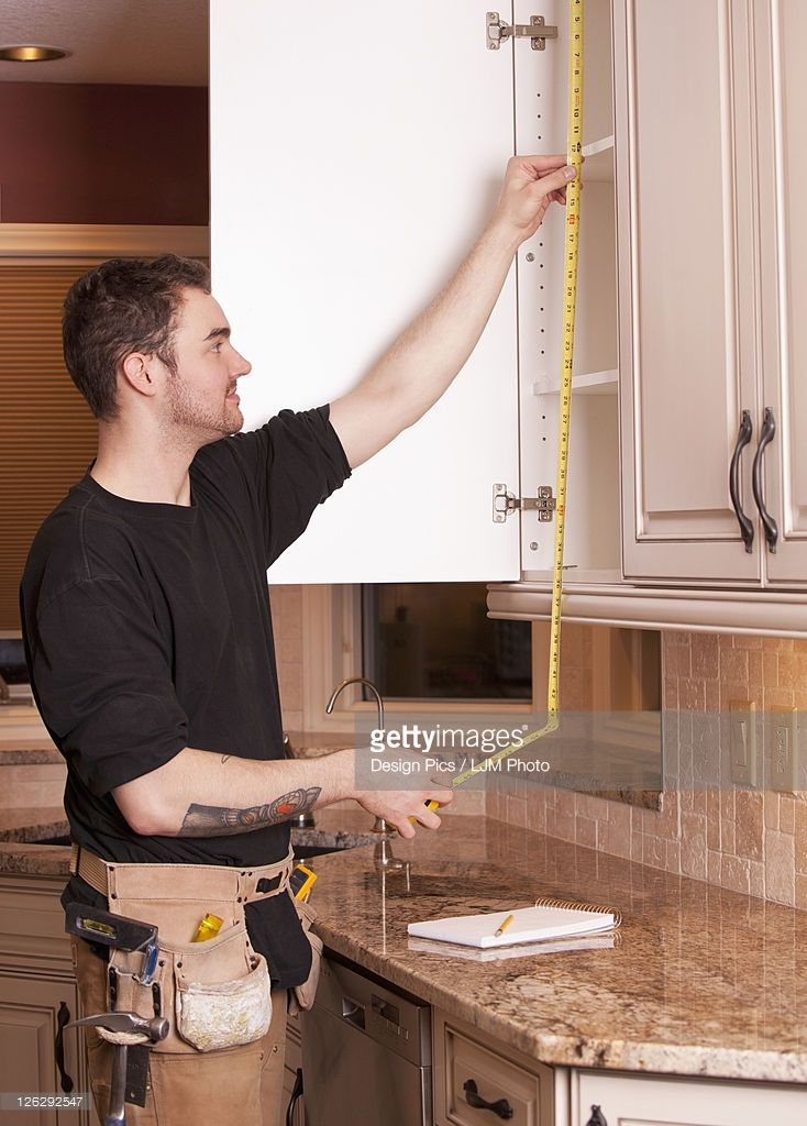 Carpenter Measuring And Installing New Kitchen Cabinets From Installing New Kitchen Cabinets
