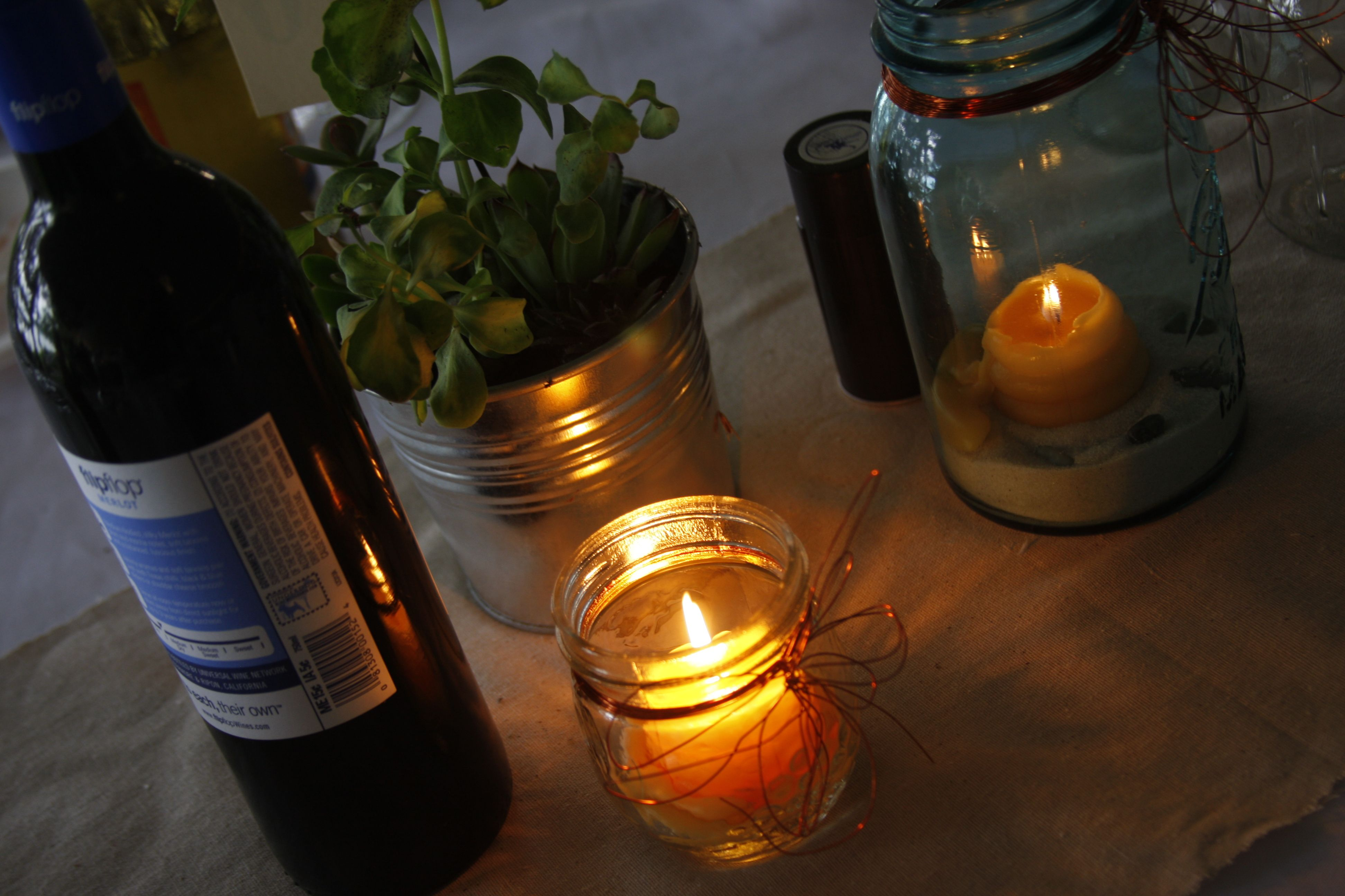Centerpieces were: potted plants in small galvanized steel buckets, a blue mason jars, clear small jelly jars with candles, sand, river rocks and copper wire. Flip Flop wine was also provided for guest on each table (one white & one red)
