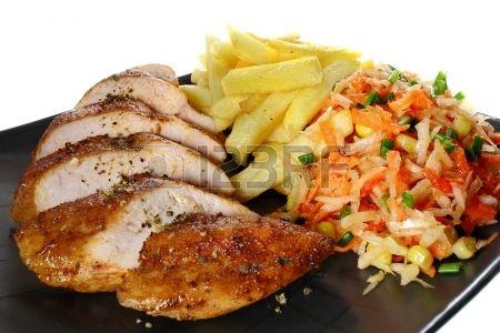 Pechuga de pollo con papas fritas franc s y ensalada de verduras Foto de archivo