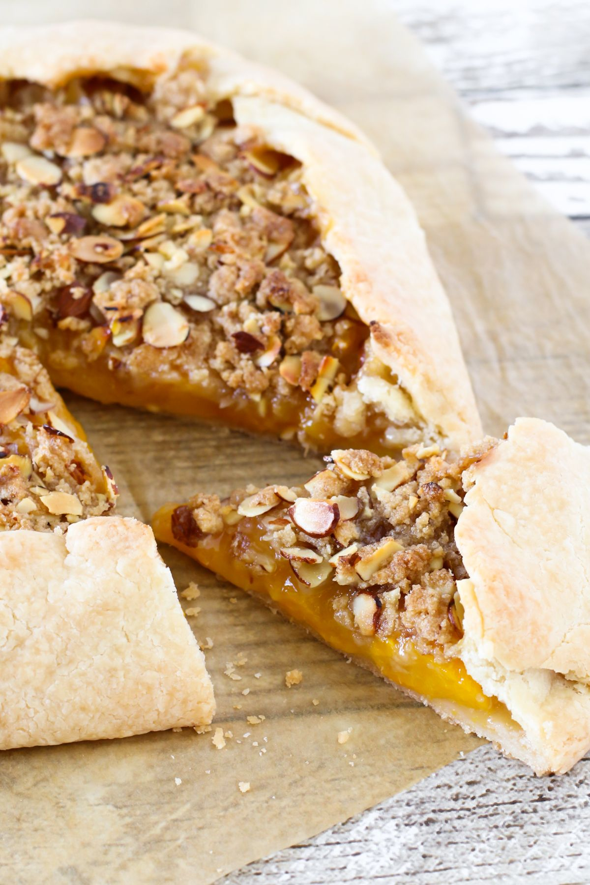 Gluten Free Vegan Peach Almond Crostata. Flaky rustic crust, filled with fresh peaches and topped with a nutty crumb topping. Baked to golden deliciousness!