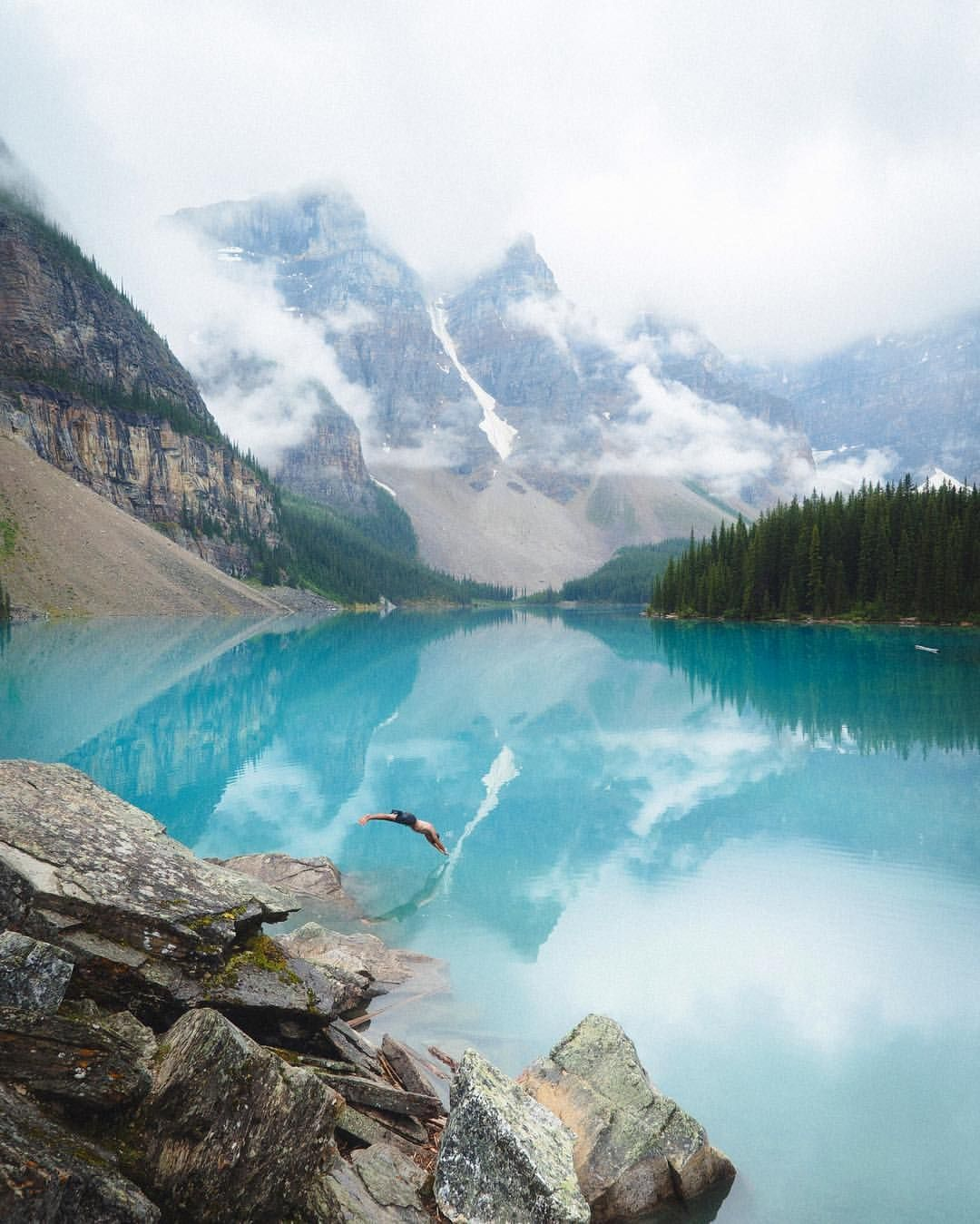 """Passion Passport on Instagram: """"""""When we first arrived, fog drowned out every peak surrounding Lake Moraine. Nothing could be seen but a near perfect reflection of the clouds. But as soon as the fog lifted, it took very little to convince my friend to dive into the cold, glacial water."""" -@babytraven Moraine Lake, Canada #passionpassport"""""""