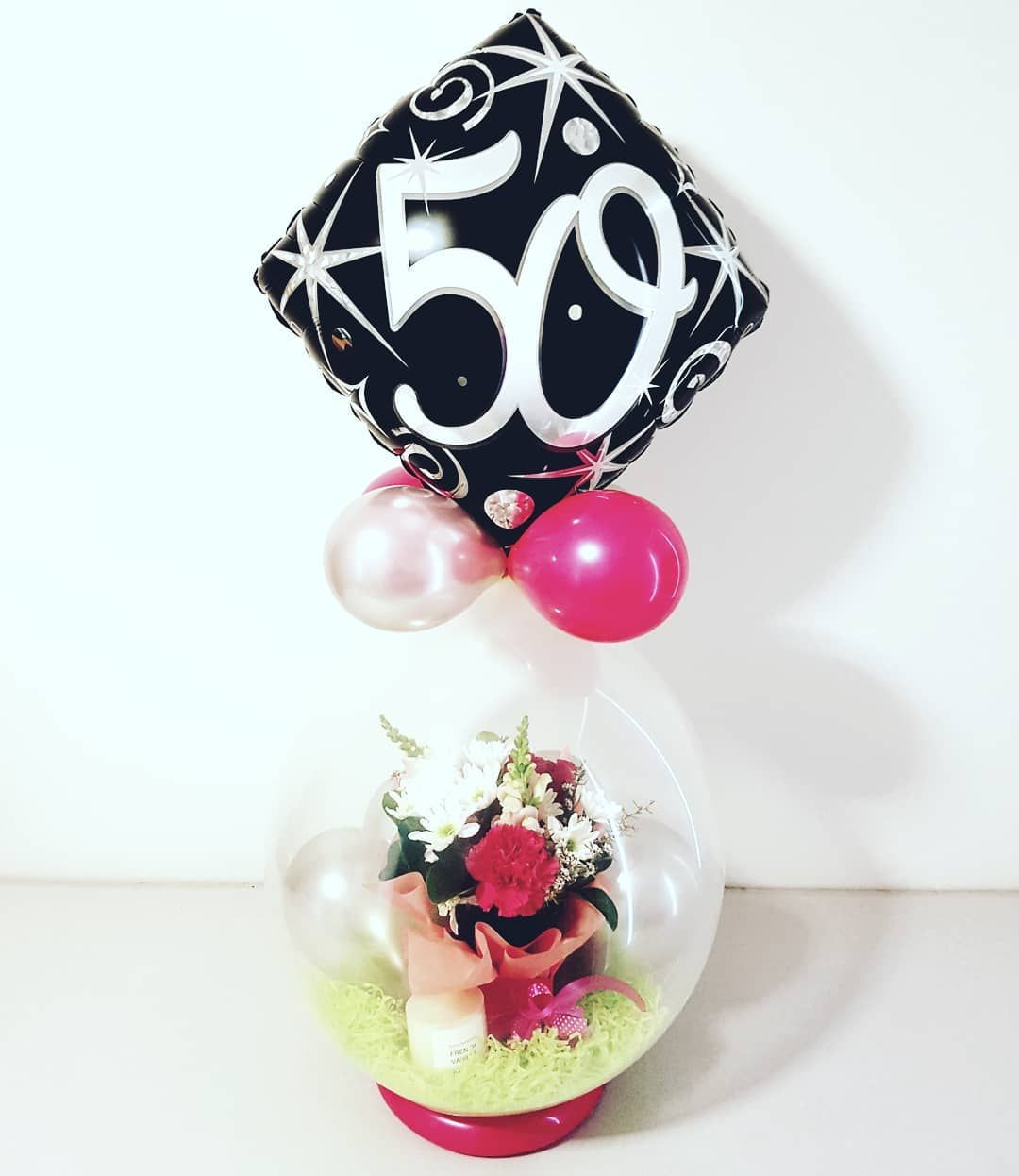 A 50th Flower Birthday Balloon With A Candle Being Taken Up The