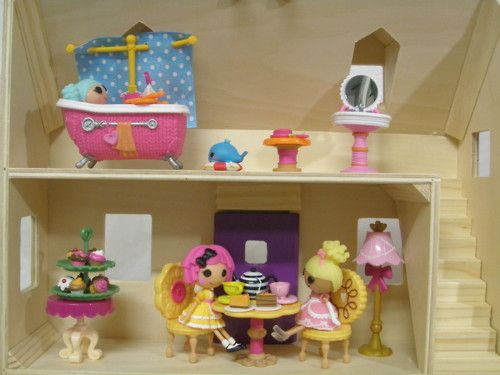 The left side of the Melissa and Doug Fold and Go Mini Dollhouse with the Lalaloopsy dolls. The furnitures are from the Lalaloopsy collection. The bakery miniature items and cupcake table and trays are from the Li'l Woodzeez Bakery Shop.