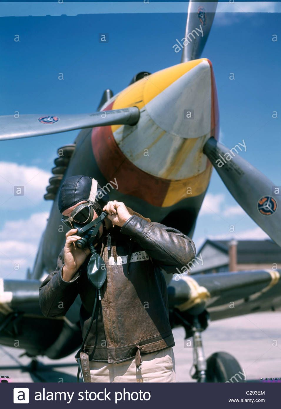 A pilot adjusts his oxygen mask in front of an airplane  Stock Photo