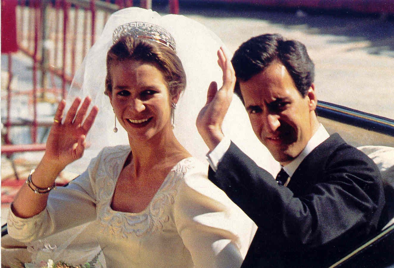 Infanta Elena and Jaime de Marichalar y Sáenz de Tejada waving to the crowd as they leave the church after their wedding ceremony.