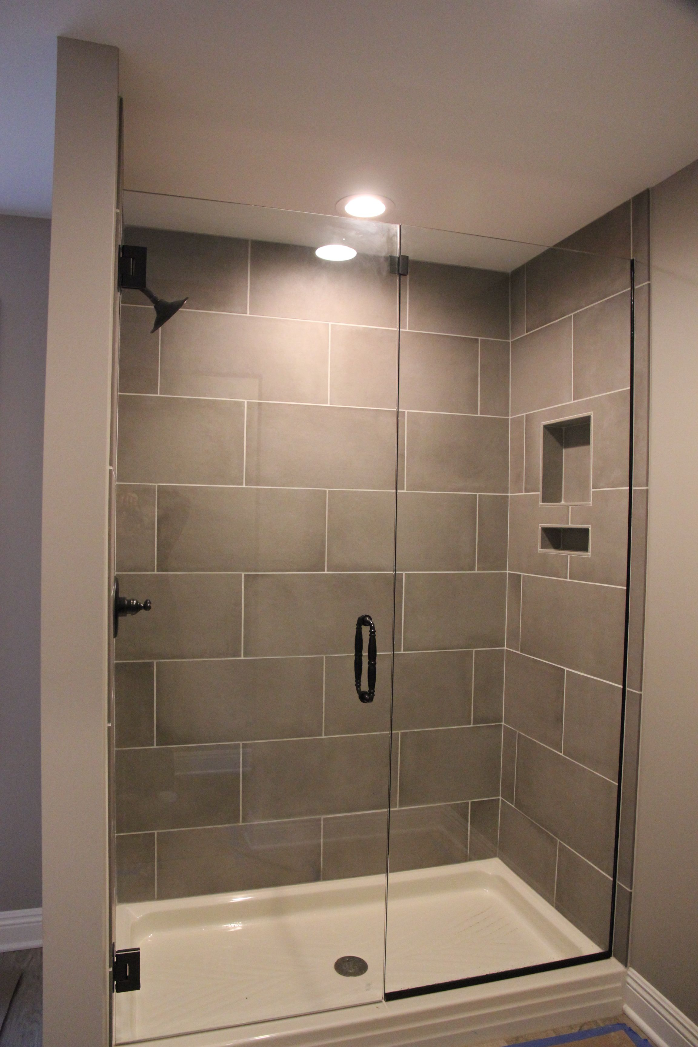 boys showers, big tiles, fiberglass base, no shower door. Easier