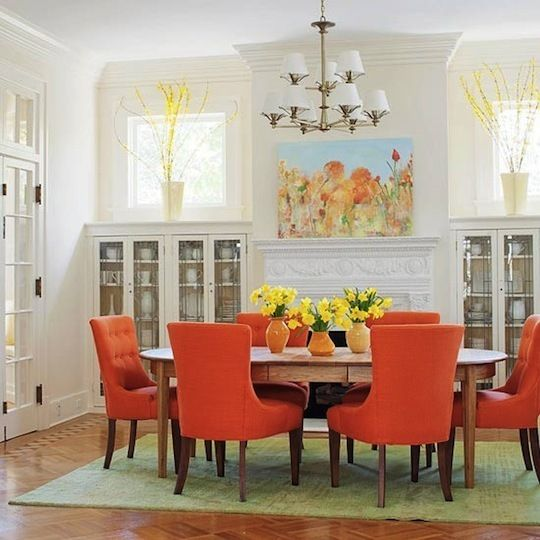 Orange chairs pop against the white wood cabinetry and walls.