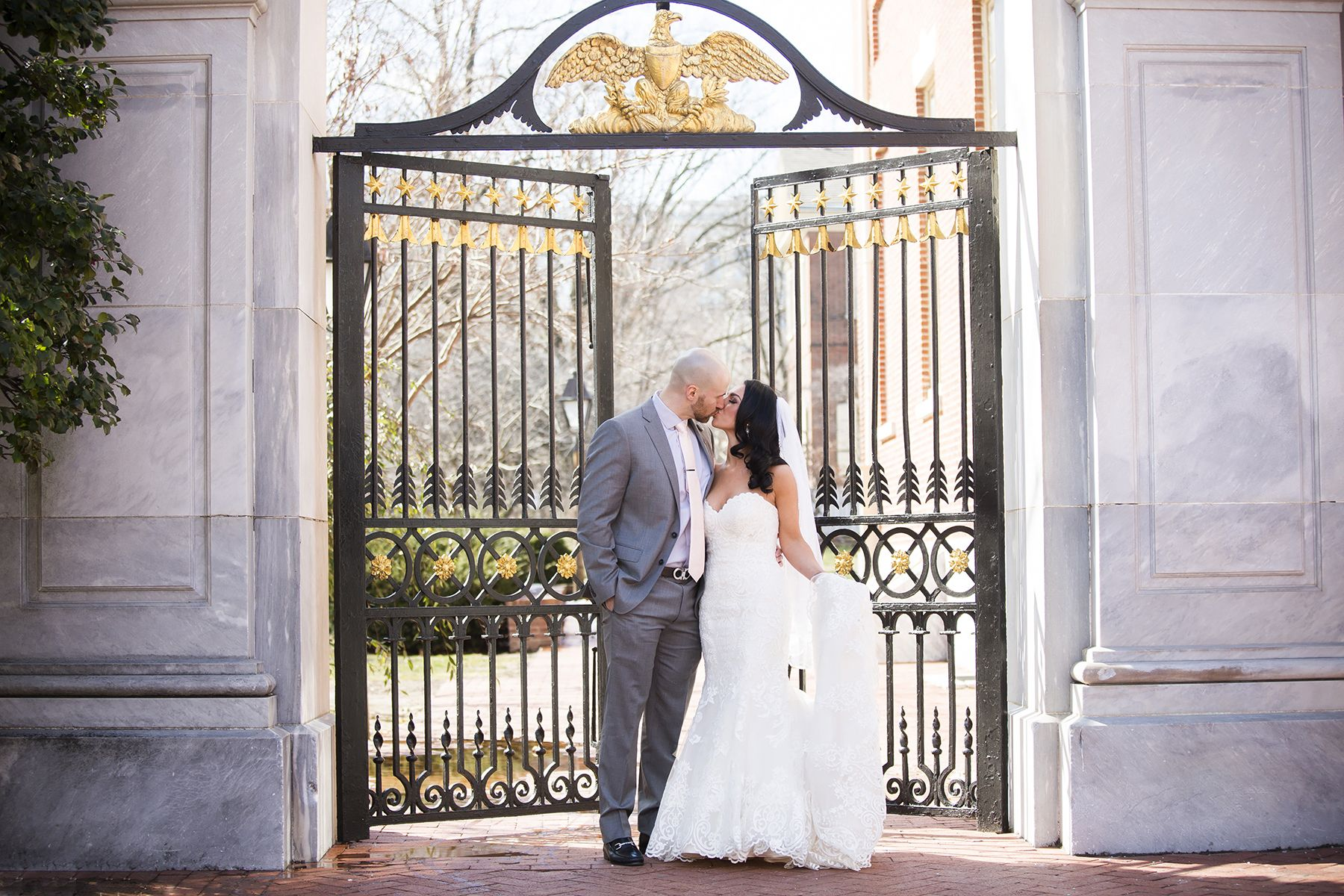 Bride and groom kiss at the first bank gate in old city philadelphia