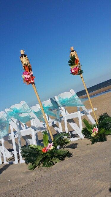 Tiki torches and Aqua blue beach wedding decor. Barefootbeachbrideoc.com
